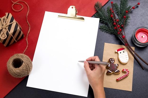 Человек, пишущий записку с вкусным рождественским домашним печеньем Premium Фотографии