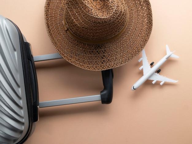 茶色の帽子とミニ飛行機とフラットレイアウトグレースーツケース Premium写真