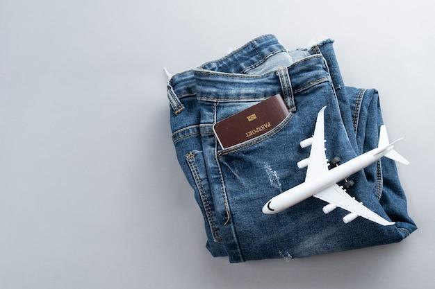 Плоский лежал мини-самолет и аксессуары для путешественников на сером фоне Premium Фотографии