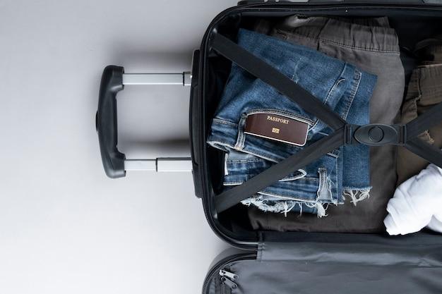 Открытый чемодан для путешествий с таиландским паспортом на сером фоне Premium Фотографии