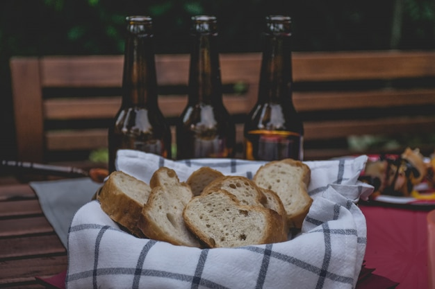パーティーやピクニックのためにテーブルの上のバスケットの場所でパンします。 Premium写真
