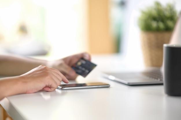 クレジットカードでモバイルスマートフォンを使用して支払いやオンライン銀行の男性の手。 Premium写真