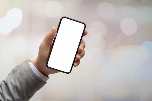 男の手が背景をぼかした写真を空白の画面のスマートフォンを保持しています。 Premium写真