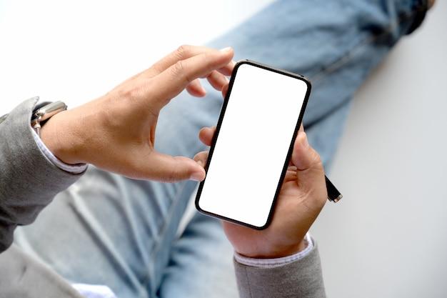 背景をぼかした写真でスマートフォンを使用して平面図男性の手。 Premium写真