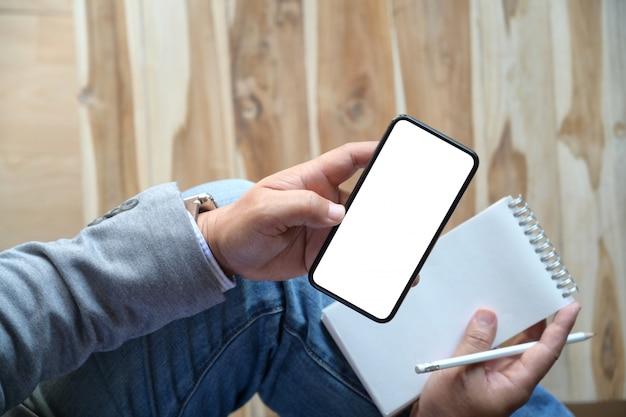 メモを書きながら携帯のスマートフォンを使用している人 Premium写真