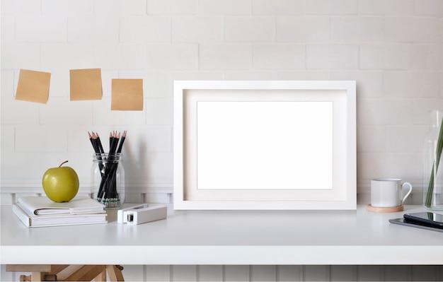 テーブルミニマリズムロフトデスクワークスペース上のポスターやフォトフレームをモックアップします。 Premium写真