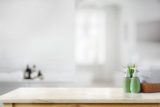 バスルームのバックグラウンドで大理石のカウンターの上に白いタオルでセラミックシャンプーボトル Premium写真