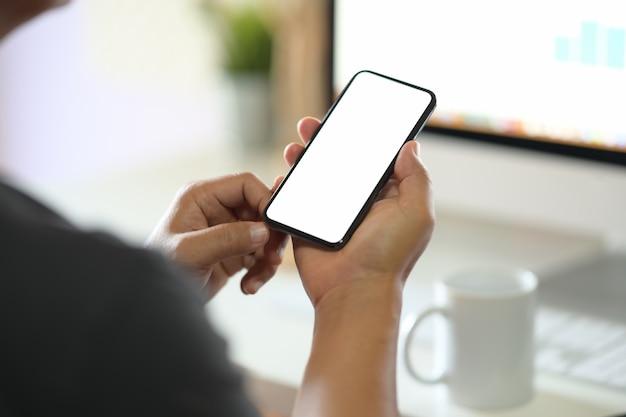 Мужчина держит пустой экран мобильного смартфона Premium Фотографии