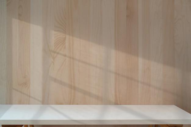 Белый стол с деревянной стеной. Premium Фотографии
