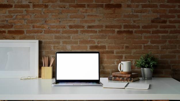 空白の額縁、空白の画面のノートパソコンとクリエイティブデスクワークスペース Premium写真