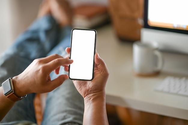 Деловой человек рука белый пустой мобильный телефон в офисе Premium Фотографии