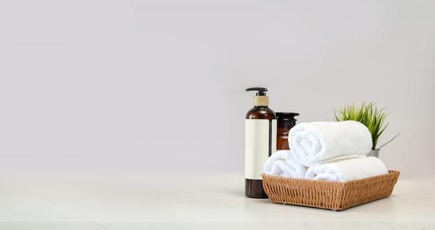 Полотенца в корзине и спа-аксессуары на столике мейбл Premium Фотографии