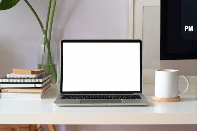 白いワークスペースにモックアップ空白の画面のノートパソコン Premium写真