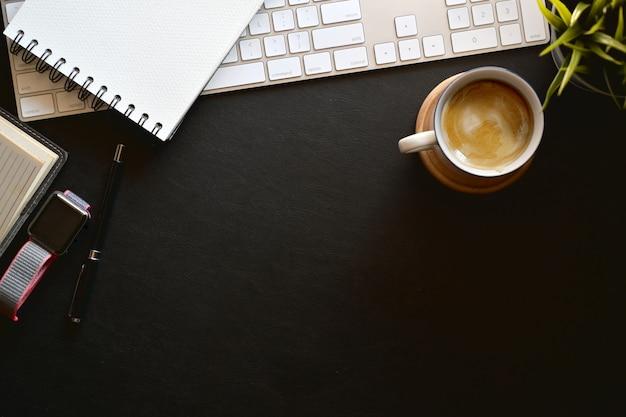 モダンなダークレザーのオフィスデスクキーボードコンピュータ、グラス、コーヒーマグ、観葉植物、コピースペース Premium写真
