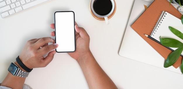 ホワイトオフィスの机でスマートフォンモックアップを使用して実業家の手のショットトップビューをトリミング Premium写真