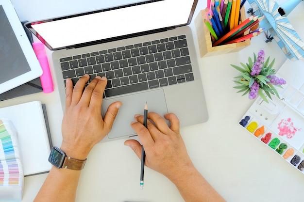 若いデザイナーが机の上のノートパソコンで作業します。 Premium写真