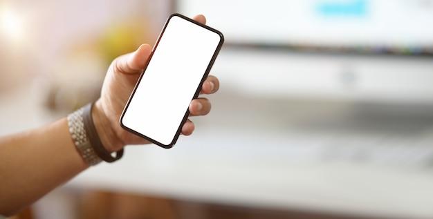 ビジネスマンのオフィスの机の上に白い画面で携帯電話をかざす Premium写真