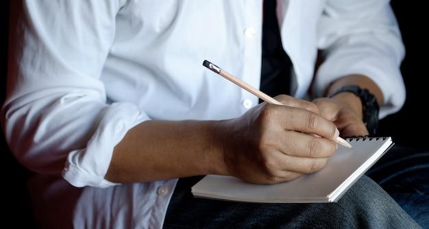 鉛筆で紙のノートに書いているその男のトリミングショット Premium写真