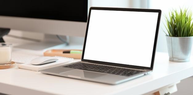 創造的な作業スペースで空白の画面のノートパソコン Premium写真