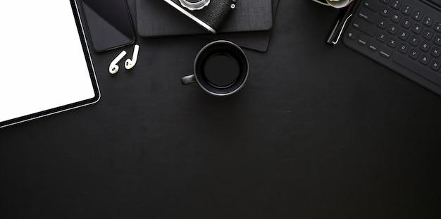 事務用品と暗いスタイリッシュな職場のトップビュー Premium写真