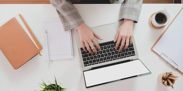 Верхняя часть руки коммерсантки печатая на портативном компьютере Premium Фотографии