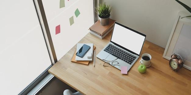 Уютный домашний офис с открытым ноутбуком с пустым экраном Premium Фотографии
