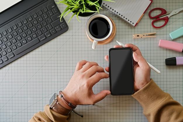 スタジオトップテーブルにモバイルのスマートフォンを保持しているグラフィックデザイナー Premium写真
