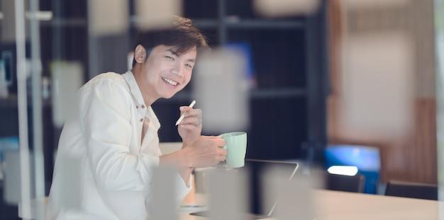 コーヒーブレークを持つ魅力的な青年実業家 Premium写真
