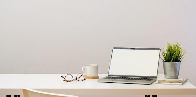 オープンブランクスクリーンのラップトップコンピューターを備えたシンプルなホームオフィス Premium写真
