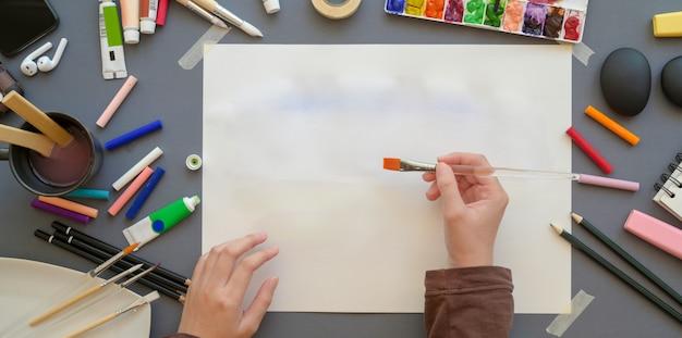 水彩、ペイントツール、ブラシで彼女のプロジェクトの女性アーティストの絵画のトップビュー Premium写真