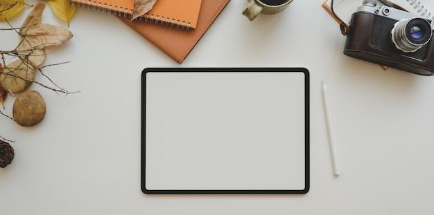 コピースペースを持つ白いテーブルに空白の画面のタブレットとオフィス用品 Premium写真