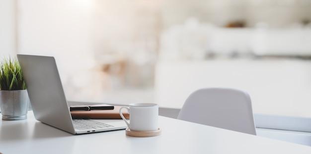 Современное рабочее место с ноутбуком, кофейной чашкой и канцелярскими товарами Premium Фотографии