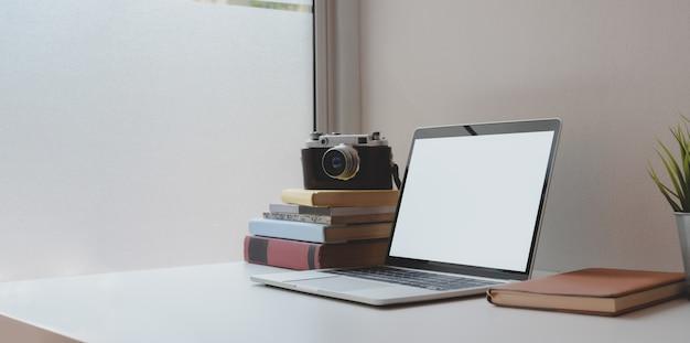 Открытый ноутбук с пустым экраном с кофейной чашкой и канцелярскими принадлежностями на удобном рабочем месте Premium Фотографии