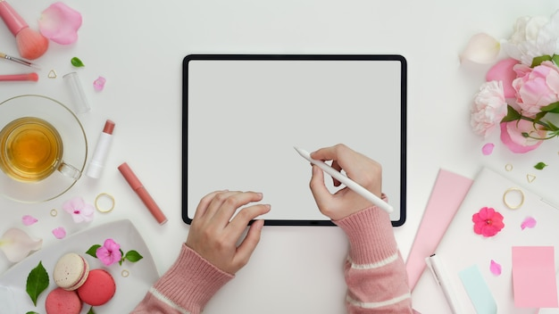 甘いピンクのフェミニンなワークスペースで空白の画面のタブレットに書いている若い女の子のトップビュー Premium写真