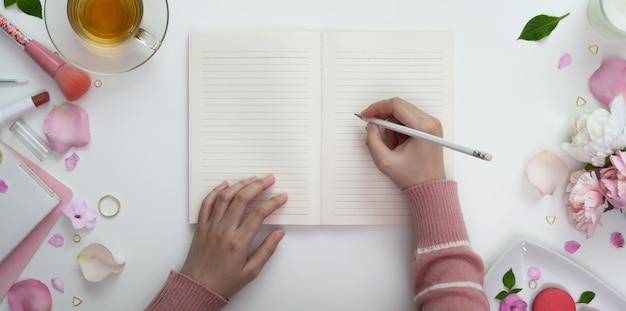 メイクアップと甘いピンクのフェミニンなワークスペースで空白のノートに書いている若い女の子のトップビュー Premium写真