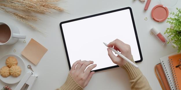 温かみのあるベージュのフェミニンなワークスペースコンセプトで空白の画面のタブレットに書く若い女性のトップビューを構成します Premium写真