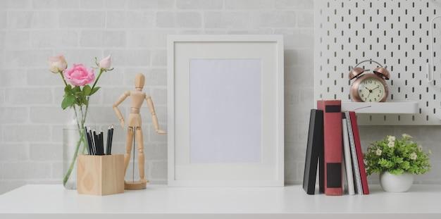 Минимальное рабочее место с макетной рамой, книгами и украшениями на белом столе и серой кирпичной стене Premium Фотографии
