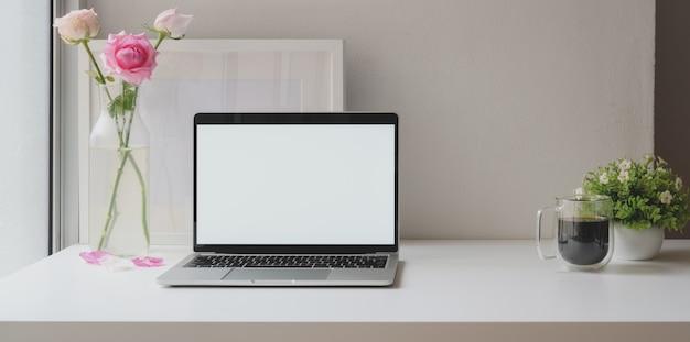 バラの花瓶とコーヒーカップのモックアップフレームで空白のラップトップコンピューターを開く Premium写真