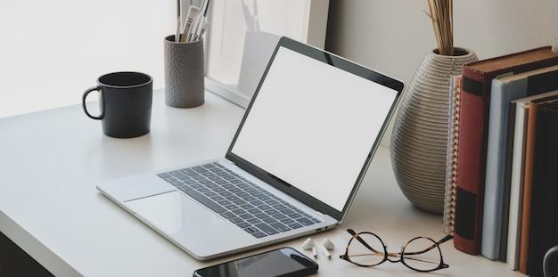 Минимальное рабочее пространство с пустым экраном ноутбука, книги, керамическая ваза Premium Фотографии