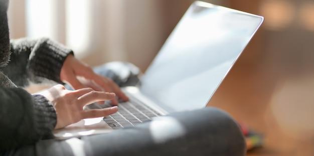 Взгляд конца-вверх молодого женского фрилансера работая над ее проектом с портативным компьютером Premium Фотографии