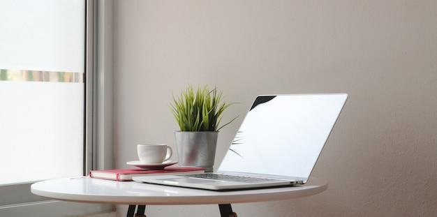 ラップトップコンピューターと白いテーブルの装飾とモダンなワークスペース Premium写真
