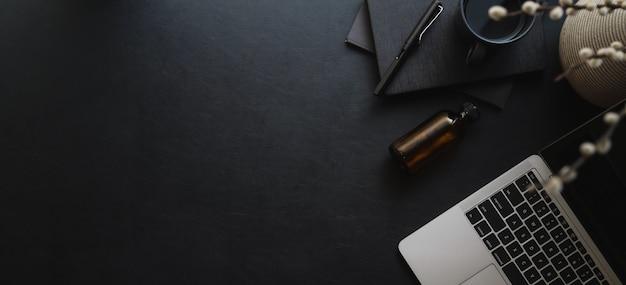 暗いモダンなワークスペースウィットラップトップコンピューターとオフィス用品とコピースペースのオーバーヘッドショット Premium写真