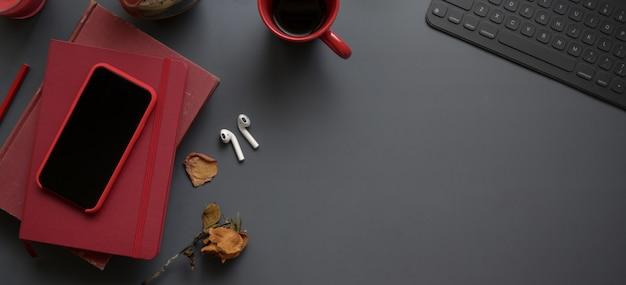 赤いノートブックとオフィス用品とコピースペースと暗い高級ワークスペースの平面図 Premium写真