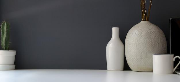 コピースペースと白いテーブルと灰色の壁にセラミック花瓶とモダンなワークスペース Premium写真