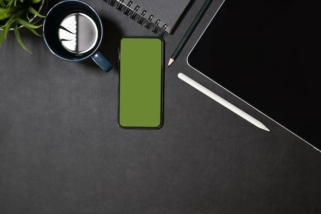 タブレット、レンズ、デザイナーガジェットを使ったクリエイティブなダークレザーデスク Premium写真