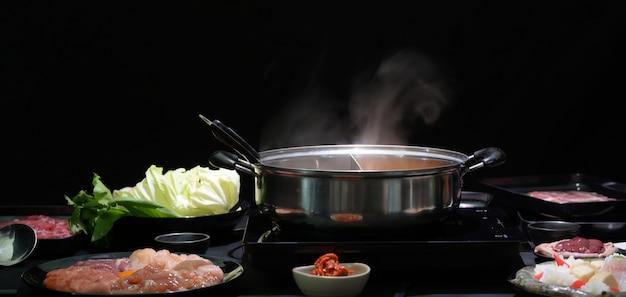 鍋、新鮮な肉、魚介類、黒の背景を持つ野菜のしゃぶしゃぶのセット Premium写真