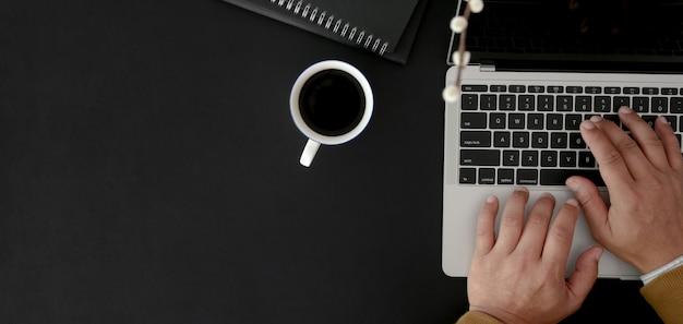 黒いテーブルに暗いモダンな職場でラップトップコンピューターに入力する実業家のトップビュー Premium写真