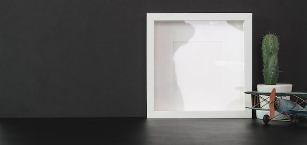 Модный кабинет с макетом кадра и копией пространства на черном столе с черной стеной Premium Фотографии