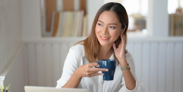 コーヒーカップを飲みながら彼女のプロジェクトに取り組んでいる若い美しい女性実業家 Premium写真