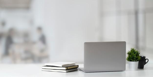 木製のテーブルとぼやけたオフィスでコピースペースに開いているラップトップコンピューターのショットをトリミング Premium写真